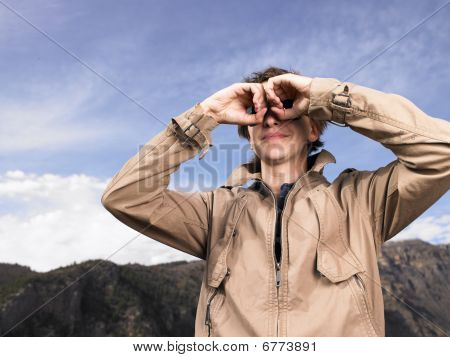 Young Man Looking Through Cupped Hands