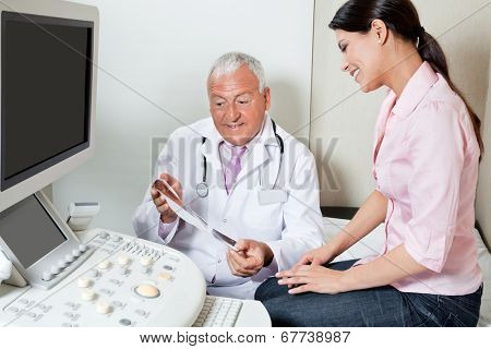 Senior male radiologist showing ultrasound print to female patient at clinic