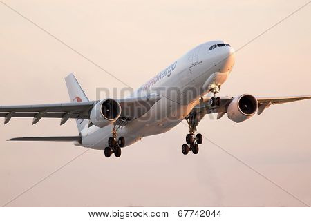 Departing MASkargo Airbus A330-223F aircraft in the sunset rays