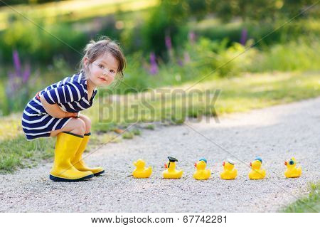 Adorable Little Girl With Rubber Ducks In Summer Park