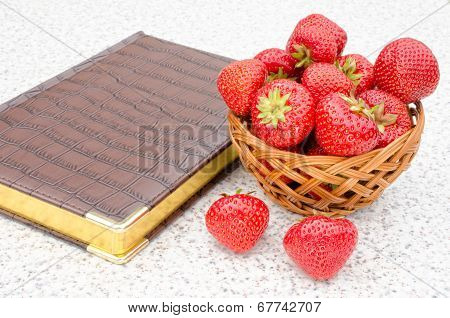 leather-bound book and ripe red strawberries