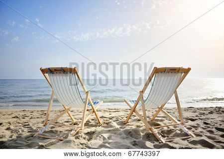 Couple Of Chairs On Sandy Beach At Sunset Looking For The Sea - Relaxation Concept