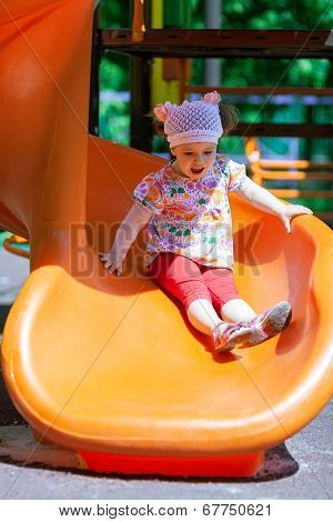 Small girl having fun on a slide