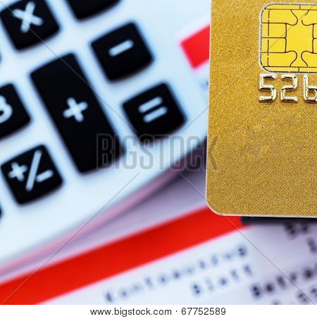 a golden credit card, bank statement and calculator. symbolic photo for cashless purchases and status symbols.