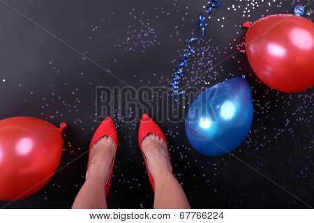 Legs with confetti and balloons on the floor