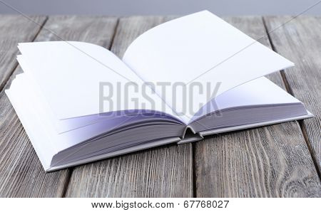 Open white book on wooden table, close-up