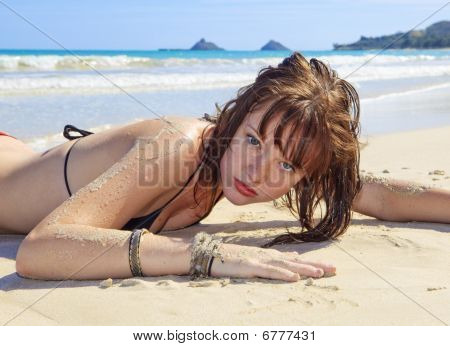 young woman in a bikini lounging on a hawaii beach