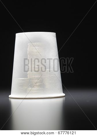 stack of coins covered by a cup