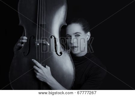Beautiful Brunette Playing A Cello With Selective Light In Black Artistic Conversion