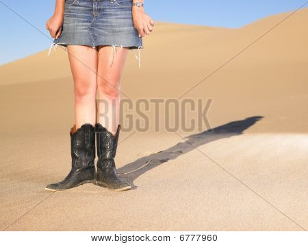 Woman Wearing Boots And Short Skirt Standing In Sand