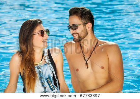 Young Couple Chatting At The Side Of A Pool
