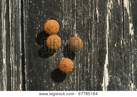 Rusty Drawing Pins Or Thumb Tacks Against A Distressed Wood Background, Macro Close Up.
