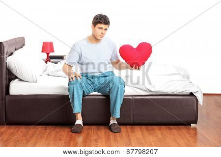 Sad guy sitting alone on bed and holding a heart isolated on white background