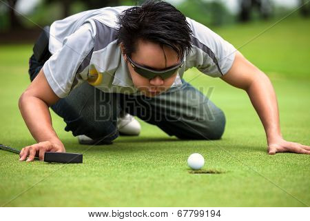 Desperate golfer blowing on golf ball to put in hole Funny golfing cheat concept