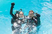 stock photo of cylinder  - Smiling couple on scuba training in swimming pool looking at camera on a sunny day - JPG