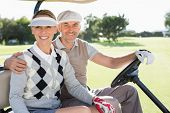 picture of buggy  - Happy golfing couple driving in their buggy smiling at camera on a sunny day at the golf course - JPG