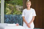 stock photo of beside  - Smiling beauty therapist standing beside massage towel at the spa - JPG