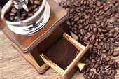 pic of coffee grounds  - Vintage coffee bean grinder and fresh ground coffee on wooden top next coffee beans - JPG