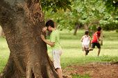 stock photo of young boy  - young boys and girls playing hide and seek in park with kid counting leaning on tree - JPG