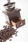 foto of coffee grounds  - Isolated vintage coffee bean grinder and fresh ground coffee next to coffee bean - JPG
