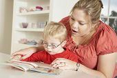 stock photo of handicap  - Downs Syndrome boy having speech therapy - JPG