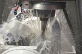 stock photo of auger  - Vertical mill cutting the metal blank with cooling liquid - JPG