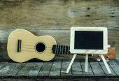 picture of ukulele  - Ukulele guitar and blank blackboard on wooden background - JPG