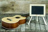 image of ukulele  - Ukulele guitar and blank blackboard on wooden background - JPG