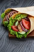stock photo of sandwich wrap  - pair of fresh juicy wrap sandwiches with chicken and vegetables on black wood table - JPG