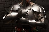 foto of stonewalled  - Closeup portrait of medieval knight keeping sword on chest on a dark stonewall background - JPG