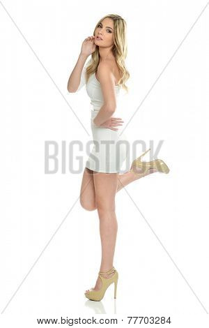 Young blond model wearing a short dress isolated on a white background