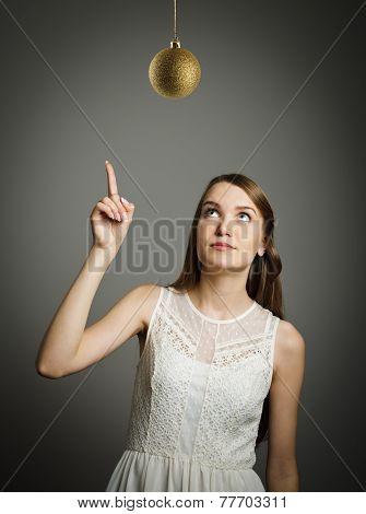 Girl Pointing At Christmas Ball.