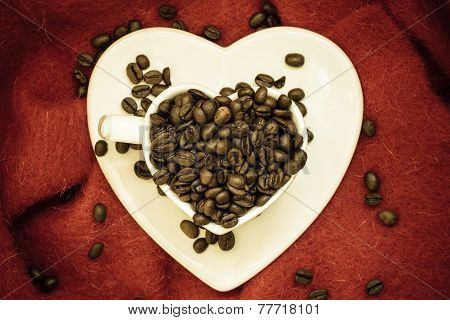 Coffee klatsch concept. Heart shaped white cup filled with roasted coffee beans on red background