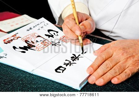 NIKKO, JAPAN - OCT 15, 2014: Hands writing japanese calligraphy Shodo on Oct 15, 2014 in Nilkko, Japan.Shodo is Japanese calligraphic art.Direct English translation for Shodo is