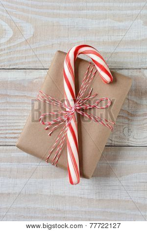 High angle shot of a large candy cane on a small plain brown paper wrapped Christmas present. Vertical format on a rustic white wooden table.