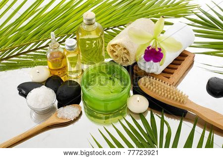 Spa Background with orchid and salt in bowl , white candle, towel, stones, oil, and palm