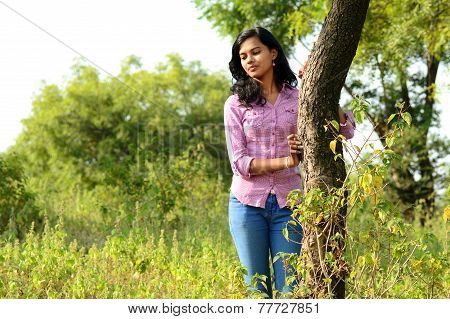 Portrait of teenage girl with tree at forest