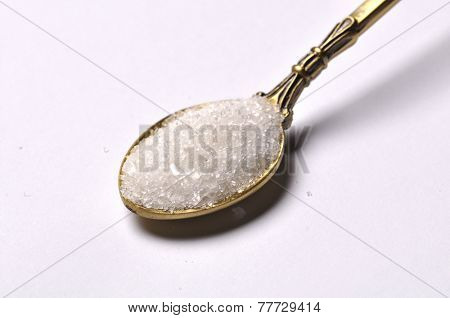 A teaspoon full of white sugar - close up