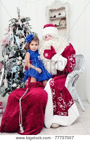 little girl in a beautiful blue dress sits on a lap at Saint Nicolas