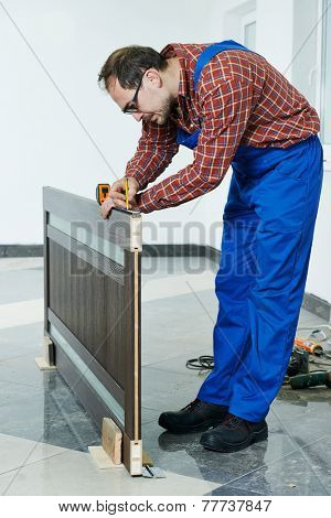 Carpenter worker preparing door leaf for installation
