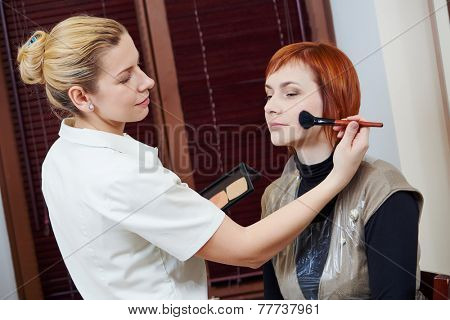 Makeup artist with paintbrush applying tonal cream to female client in beauty salon
