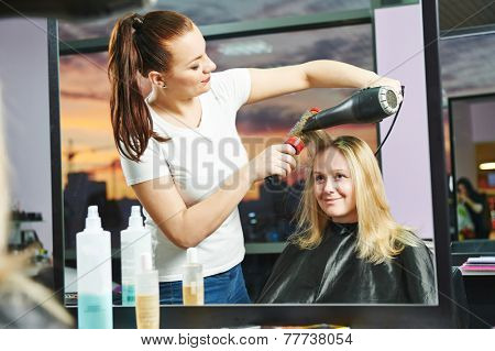hairdresser drying hair with blow dryer of woman client at beauty parlour after highlighting