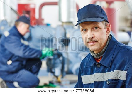 portrait of service engineer worker at industrial compressor station for refrigeration at manufacturing factory