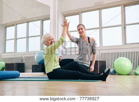 Senior Woman Giving High-five To Her Personal Trainer