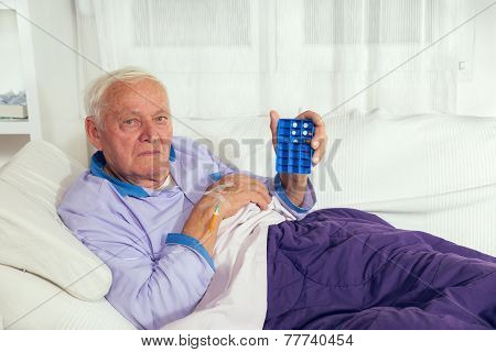 Senior man uses a pill organizer to prepare his medication for the week.