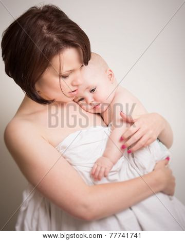 Young Mother In Intimate Cuddle With Her Baby