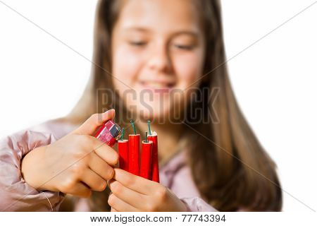 Little girl holding a firecracker. Selective focus.