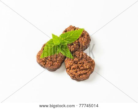 overhead view of three wholegrain chocolate chip cookies with fresh mint
