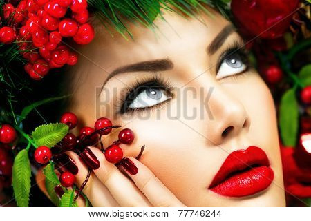 Christmas fashion model woman face close up. Xmas New Year hairstyle and make up. Beauty Girl. Gorgeous Vogue style Lady with decorations on her head, baubles, professional makeup, red lipstick, nails