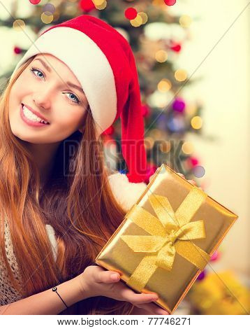Christmas Gift. Happy Surprised Girl opening Gift box at home. Pretty young woman portrait. Christmas Tree